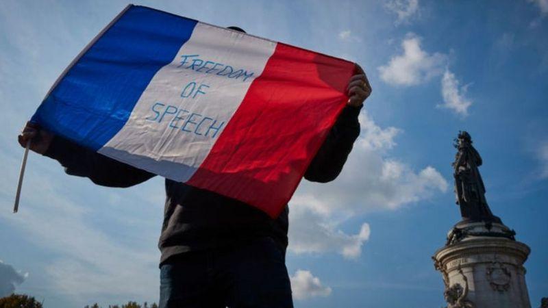 প্যারিসে শিক্ষক হত্যাকান্ডের বিরুদ্ধে বিক্ষোভে ফরাসী পাতাকার ওপর স্লোগান 'মত প্রকাশের স্বাধীনতা'